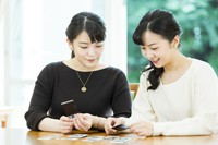 Princess Mako, left, and Princess Kako look at the photos they took at the Akasaka Estate in Tokyo's Minato Ward, on Oct. 6, 2020. (Photo courtesy of the Imperial Household Agency)