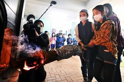 二十四節季の霜降の日に合わせて行われた「火入れ式」。ストーブに火をつける六甲山小学校の児童たち=神戸市灘区で2020年10月23日午前10時25分、望月亮一撮影