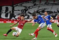新型コロナウイルスの流行による中断を挟み、リーグ戦が再開した7月4日の浦和戦でクロスを上げる横浜マの天野純(右)。この試合はスコアレスドローだった=埼玉スタジアムで2020年7月4日、宮間俊樹撮影