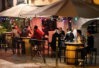 People drink in a bar terrace before the start of a new coronavirus curfew, in Bayonne, southwestern France, on Oct. 22, 2020. (AP Photo/Bob Edme)