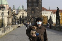 A man wearing a face mask carries his dog across the medieval Charles Bridge in Prague, Czech Republic, on Oct. 21, 2020. (AP Photo/Petr David Josek)