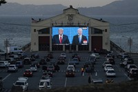 People watch from their vehicles as President Donald Trump, on left of video screen, and Democratic presidential candidate former Vice President Joe Biden speak during a Presidential Debate Watch Party at Fort Mason Center in San Francisco, on Oct. 22, 2020. (AP Photo/Jeff Chiu)