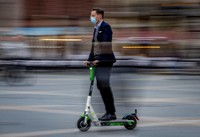 A man wearing a face mask travels by scooter on the Opera square in Frankfurt, Germany, on Oct. 22, 2020. (AP Photo/Michael Probst)