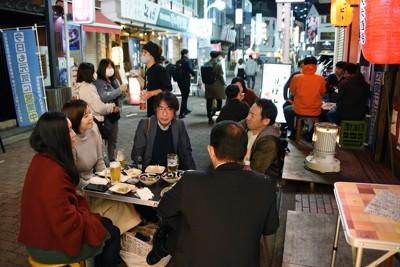 新型コロナウイルス対策の路上営業を始めた飲食店でテーブルを囲む人たち=長野県松本市で2020年10月16日、丸山博撮