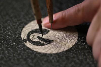 「紋章上繪師」は竹製のコンパスと極細の筆、墨、定規などを巧みに使い、繊細で美しい家紋を描く=東京都台東区で2020年9月17日、佐々木順一撮影