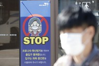 A man wearing a face mask walks past near a banner showing precaution against the coronavirus, at the Imjingak Pavilion in Paju, South Korea, on Oct. 23, 2020. (AP Photo/Lee Jin-man)