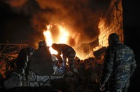 People try to remove car tyres from a car shop on fire after shelling by Azerbaijan's artillery during a military conflict in Stepanakert, the separatist region of Nagorno-Karabakh, on Oct. 23, 2020. (AP Photo)