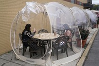 In this Oct. 22, 2020 photo, Aviva Markowitz, left, and Rivka Alter enjoy a drink in a protective bubble at the Lazy Bean Cafe in Teaneck, New Jersey. (AP Photo/Seth Wenig)
