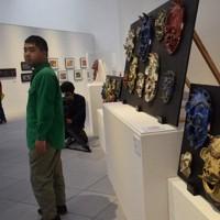 「鬼活の面」の作品群と中野さん(左)