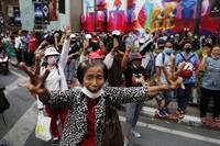 Pro-democracy protesters gather, flashing three-fingered salutes near a main shopping district in Bangkok, Thailand, on Oct. 25, 2020. (AP Photo/Gemunu Amarasinghe )