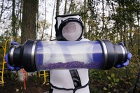 Sven Spichiger, Washington State Department of Agriculture managing entomologist, displays a canister of Asian giant hornets vacuumed from a nest in a tree behind him Saturday, Oct. 24, 2020, in Blaine, Wash. (AP Photo/Elaine Thompson)