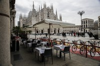 In this Wednesday, Oct. 21, 2020 file photo, empty tables of a restaurant in the Duomo Square in Milan, Italy. (AP Photo/Luca Bruno, File)
