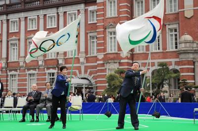 全国を巡回し東京に戻ってきた五輪旗とパラリンピック旗を振る小池百合子東京都知事(左)と桜田義孝五輪担当相(当時)。五輪とパラリンピックは同一都市での連続開催が原則だ=東京都千代田区のJR東京駅前で2019年3月30日、梅村直承撮影