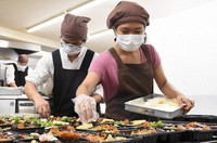 A student from Myanmar, right, is seen putting food items into a lunchbox in the kitchen of bento shop Hidamari, in Kobe's Hyogo Ward, on Aug. 25, 2020. (Mainichi/Kwanghoon Han)