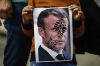 A child holds a photograph of France's President Emmanuel Macron, stamped with a shoe mark, during a protest against France in Istanbul, on Oct. 25, 2020. (AP Photo/Emrah Gurel)