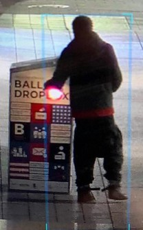 This surveillance image provided by the Boston Police Department shows a man approaching a ballot drop box outside the Boston Public Library, early Sunday, Oct. 25, 2020, in downtown Boston. (Courtesy of Boston Police Department via AP)