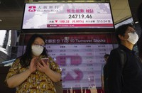 People walk past a bank's electronic board showing the Hong Kong share index at Hong Kong Stock Exchange on Oct. 27, 2020.  (AP Photo/Vincent Yu)