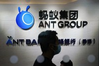 In this Oct. 23, 2020, photo, an employee walks past a logo of the Ant Group at their office in Hong Kong. (AP Photo/Kin Cheung)