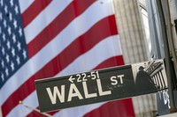 In this Sept. 21, 2020 file photo, a Wall Street sign is framed by a giant American flag hanging on the New York Stock Exchange in New York. (AP Photo/Mary Altaffer)