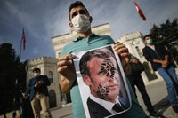 A youth holds a photo of France's President Emmanuel Macron, stamped with a shoe mark, during a protest against France in Istanbul, Turkey, on Oct. 25, 2020. (AP Photo/Emrah Gurel)