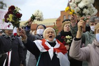 People, most of them pensioners, wave bunches of flowers during an opposition rally to protest the official presidential election results in Minsk, Belarus, on Oct. 26, 2020. (AP Photo)