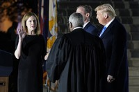 U.S. President Donald Trump watches as Supreme Court Justice Clarence Thomas administers the Constitutional Oath to Amy Coney Barrett on the South Lawn of the White House in Washington on Oct. 26, 2020, after Barrett was confirmed by the Senate earlier in the evening. (AP Photo/Patrick Semansky)