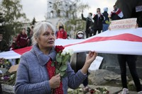 A woman holds red and white roses and an old Belarusian national flag during an opposition rally to protest the official presidential election results in Minsk, Russia, on Oct. 26, 2020. (AP Photo)