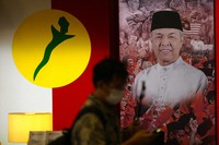 A man walks in front of a poster of UMNO ( United Malays National Organisation) President Ahmad Zahid at UMNO headquarter in Kuala Lumpur, Malaysia, on Oct. 26, 2020. (AP Photo/Vincent Thian)