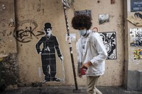 A man wearing a face mask walks by a Charlie Chaplin street art in the Montmartre district of Paris, on Oct.25, 2020.  (AP Photo/Lewis Joly)