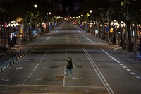 A resident walks with a dog on an empty street after curfew in Barcelona on Oct. 25, 2020. (AP Photo/Emilio Morenatti)