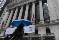A woman with an umbrella passes the New York Stock Exchange on Oct. 26, 2020. (AP Photo/Mark Lennihan)