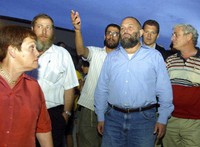 Israel's then-Infrastructure Minister Effie Eitam, center in blue shirt, listens to Jewish settlers when visiting Mitzpeh Assaf, an illegal outpost which Israel's Defense Minister said will be dismantled, near the settlement of Ofra, north of Jerusalem, on Oct. 13, 2002. (AP Photo/Zoom 77)