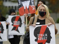 Women's rights activists with posters of the Women's Strike action protest against recent tightening of Poland's restrictive abortion law in front of the parliament building while inside, guards had to be used to shield right-wing ruling party leader Jaroslaw Kaczynski from angry opposition lawmakers, in Warsaw, Poland, on Oct. 27, 2020. (AP Photo/Czarek Sokolowski)