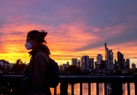 A woman wearing a face mask walks over a bridge with the buildings of the banking district in background in Frankfurt, Germany, on Oct. 26, 2020. (AP Photo/Michael Probst)