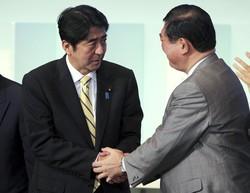 2012年の自民党総裁選の決選投票で石破茂氏(右)に逆転勝利し、総裁に選出された安倍晋三氏。この時、石破氏は安倍氏にとって「脅威」だった(自民党本部で2012年9月26日)(Bloomberg)