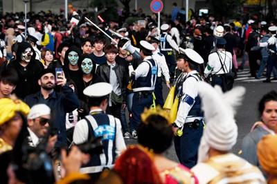 昨年の渋谷駅前。警察官の指示に従い、仮装した人たちが横断歩道を渡っていく=2019年11月1日未明、滝川大貴撮影