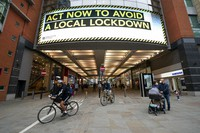 In this Sept. 22, 2020 file photo, members of the public are seen by a public information message in Manchester, England. (AP Photo/Jon Super)