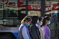 Women wearing face masks to help curb the spread of the coronavirus walk past a moving bus on a street in Beijing, on Oct. 28, 2020. (AP Photo/Andy Wong)