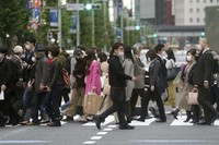 People wearing protective masks walk across a pedestrian crossing in Tokyo on Oct. 28, 2020. (AP Photo/Eugene Hoshiko)