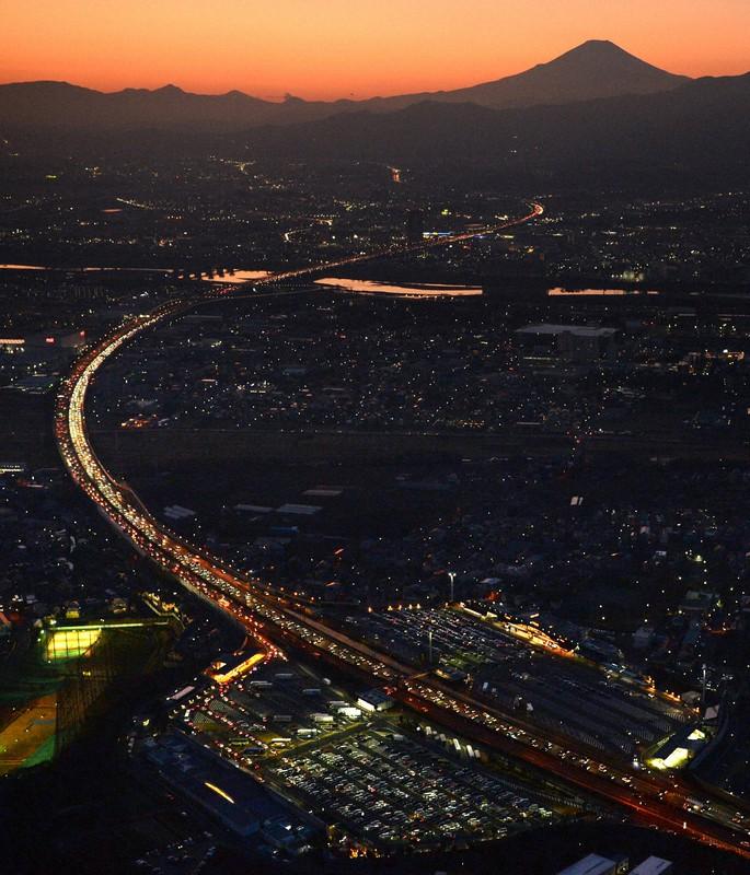 世界一高い日本の高速道路料金は韓国の8倍(Uターンラッシュなどで混雑する東名高速道路の上下線。手前が東京方面で、下は海老名SA。奥は富士山で2020年1月3日午後5時5分、本社ヘリから丸山博撮影)