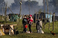 A family stands with their pet dog and belongings after their shack home was destroyed by police carrying out the eviction of a squatters camp in Guernica, Buenos Aires province, Argentina, on Oct. 29, 2020. (AP Photo/Natacha Pisarenko)