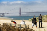 With the Golden Gate Bridge in the background, walkers wear masks while strolling at Crissy Field East Beach in San Francisco on Oct. 22, 2020. (AP Photo/Noah Berger)