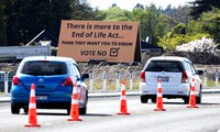 In this Oct. 16, 2020, file photo, cars are driven past a billboard urging voters to vote