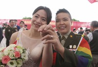 Lesbian couple Yi Wang, right, and Yumi Meng show their wedding rings during a military mass weddings ceremony in Taoyuan city, northern Taiwan, on Oct. 30, 2020. (AP Photo/Chiang Ying-ying)