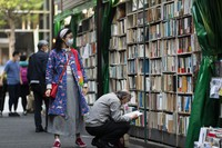 People wearing face masks shop around at a secondhand book store in Tokyo on Oct. 29, 2020. (AP Photo/Hiro Komae)