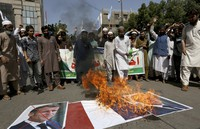 Supporters of the Muslims Students Organization burn a representation of a French national flag and defaced images of French President Emmanuel Macron during a protest against the president and against the publishing of caricatures of the Prophet Muhammad in Karachi, Pakistan, on Oct. 30, 2020. (AP Photo/Fareed Khan)
