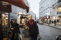 A man wearing a golden mask costume walks down a street in Paris on Oct.29, 2020. (AP Photo/Lewis Joly)