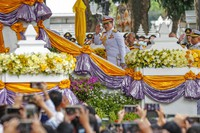 King Maha Vajiralongkorn, center, waves as he arrives to participate in a graduation ceremony at Thammasat University in Bangkok, Thailand, on Oct. 30, 2020. (AP Photo/Sakchai Lalit)