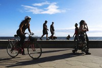 People are seen walking and cycling along the St Kilda Beach Promenade in Melbourne, Australia, on Oct. 28, 2020. Melbourne, Australia's former coronavirus hot spot, emerged from a lockdown at midnight Tuesday, restaurants, cafes and bars were allowed to open and outdoor contact sports can resume. (AP Photo/Asanka Brendon Ratnayake)