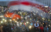 In this Aug. 19, 2020 file photo, Belarusian opposition supporters light their phone lights and wave old Belarusian national flags during a protest rally in front of the government building at Independent Square in Minsk, Belarus. (AP Photo/Dmitri Lovetsky)